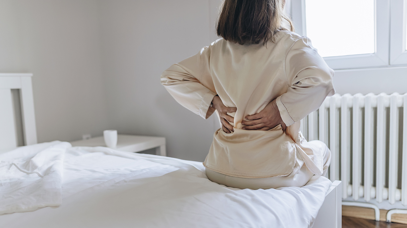 A woman massages her sore back