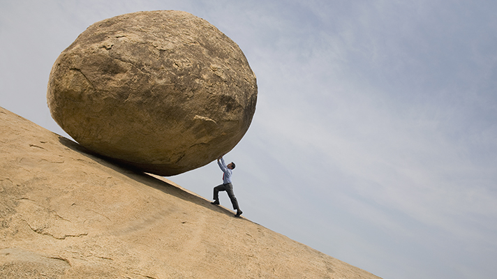 Person rolling a boulder uphill