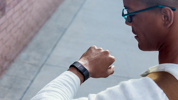 A man wearing a Fitbit Charge 2 device