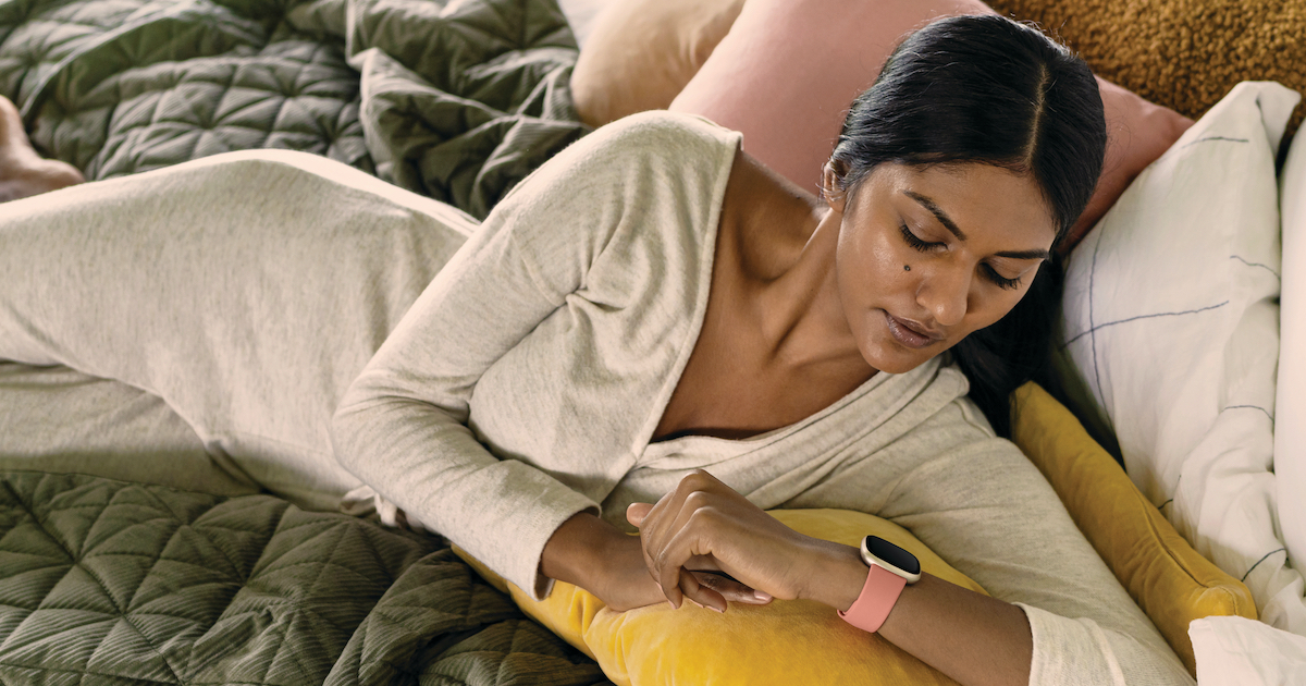 A person reclines on a bed and examines a Fitbit watch screen
