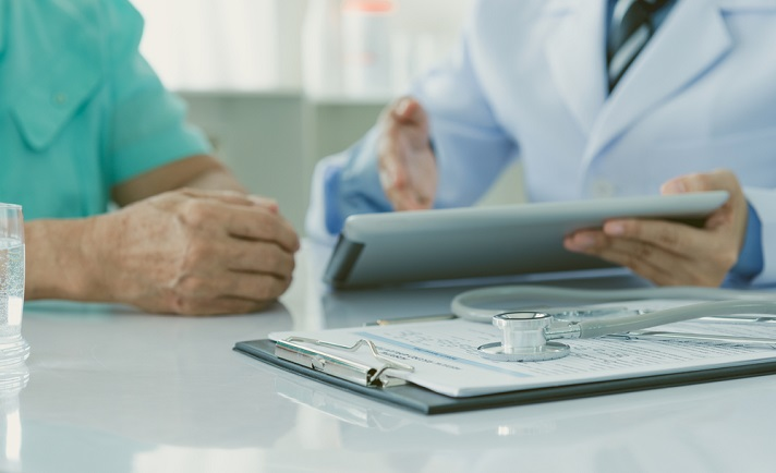 Doctor reviewing medical records on a tablet with a patient