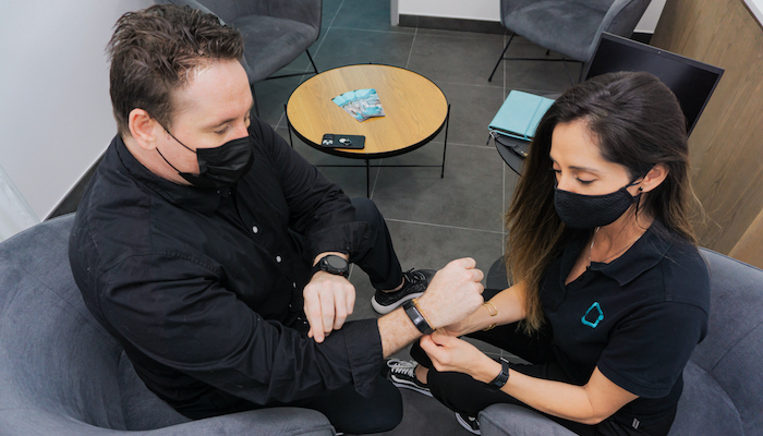 Person putting a smart device on another's wrist