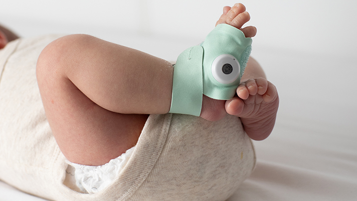 A product shot of the Owlet Smart Sock V3 on an infant