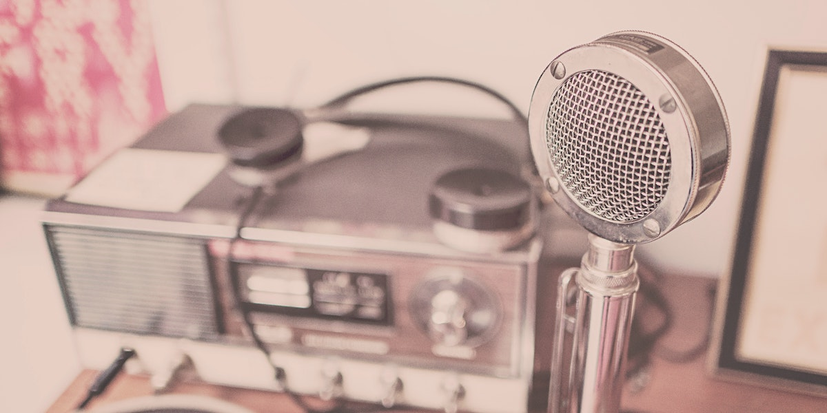 An old-time radio with microphone on a desk represents the podcast