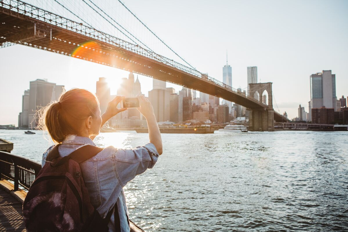 Person next to bridge taking photo with a smartphone