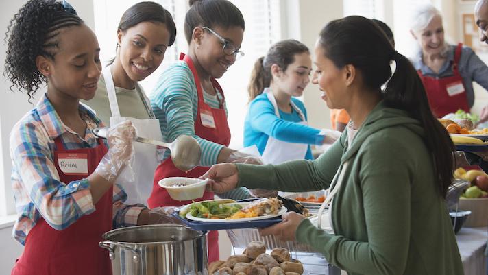 Volunteers serving food at community kitchen Mobi   Getty.'