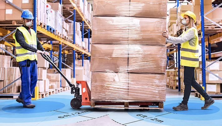 Two workers in vests and masks move a pallet of boxes with a machine lift.