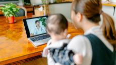 A mother and child during a telehealth video visit