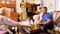 Papa Pal playing chess with woman