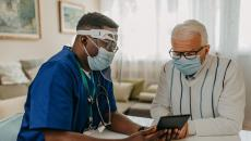 Patient in mask with healthcare worker in PPE