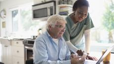 Home healthcare professional and client discuss instructions on a pill bottle