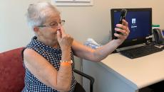 A patient uses a smartphone screening test to analyze stroke-like symptoms she's experiencing.