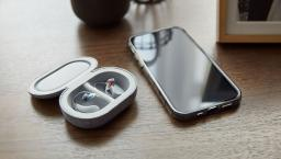 Bose SoundControl Hearing Aids in their case on a table next to an iPhone