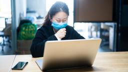 Person sitting at a desk on their laptop wearing a mask while they cough
