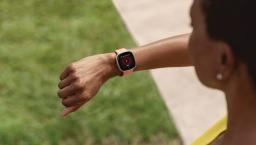 Person observes Fitbit watch on wrist