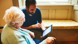 An aide helps a senior operate a tablet device