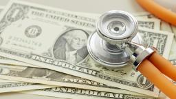 A stethoscope rests on dollar bills