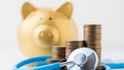 A piggy bank next to a pile of coins and a stethoscope.