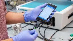 Penn researcher holding a smartphone as it uses the RAPID test to detect COVID-19
