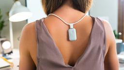 Person wearing the Upright GO S on the necklace while working at a desk