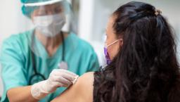 Healthcare professional in a mask swabs patient arm with cotton before administering a vaccine