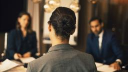 Rear view of a person sitting at a table in a business meeting