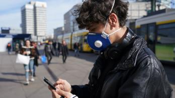Man in mask uses smartphone