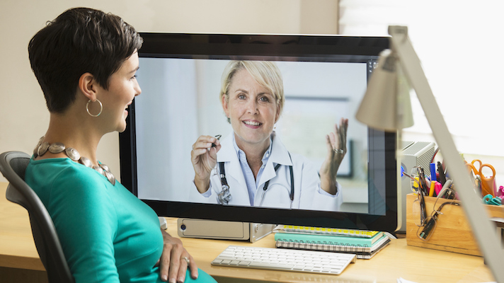 A woman conducts a telemedicine visit.