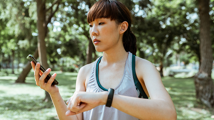 Person outdoors looks at smartphone